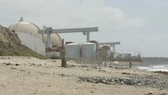 Beach hill pan to Nuclear powerplant Stock Footage