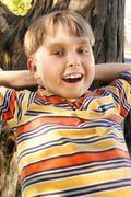 Smiling child in dapled sunlight Stock Photos