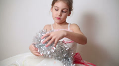 Little girl sits in a beautiful white dress with tinsel Stock Footage