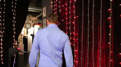 Man enters the erotic museum-shop with garlands and statuettes Stock Footage
