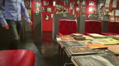 Man flipping book sitting red sofa in intim museum-shop Stock Footage