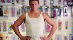 Muscular man in a white vest and jeans at the intim shop Stock Footage