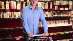 Man in store with shopping cart and clothes agains of lingerie Stock Footage