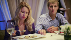 Cute girl feeding the man with a spoon in restaurant Stock Footage