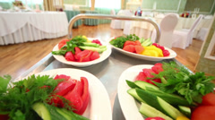 Four plates with fresh vegetables driving on trey at restaurant Stock Footage