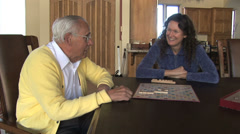 Senior Man/ Young Woman Play Board Game Stock Footage