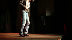 Legs of man in jeans dancing flamenco on dark stage Stock Footage