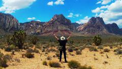 Man Walks In Desert Lifts Hands Skyward In Moment Of Awe Stock Footage