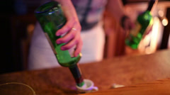 Hands of bartender lighting two bottles in night club. Stock Footage
