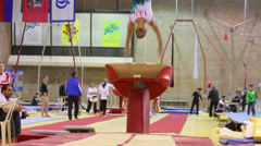 Slim girl jumps over vaulting buck in Hall Dynamo Stadium Stock Footage