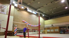 Girl trains oneself on horizontal bar and trainer looks at her - stock footage