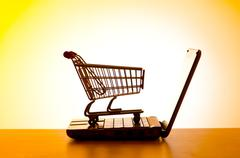 Silhoette of shopping cart and laptop Stock Photos