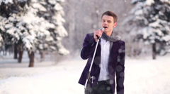 Singer in suit and scarf sings holding microphone outdoors Stock Footage