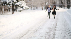 Young happy man and woman run on pathway in winter park Stock Footage