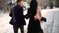 Back of young happy man and woman running on pathway in winter park Stock Footage