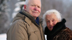 Happy elderly husband and wife smile and caress in park - stock footage