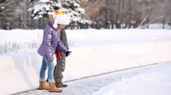 Happy brother and sister run up snowdrift and whirl in park Stock Footage
