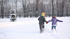 Back of boy and girl running and falling in snowdrift Stock Footage