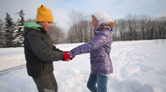 Brother and sister spin in snowdrift in park at winter day Stock Footage
