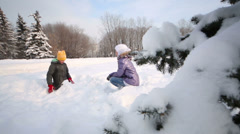 Brother and sister sit and throw up snow in snowdrift in park Stock Footage