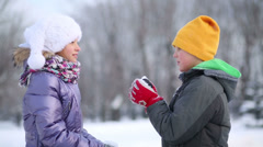 Happy boy and girl throw snow in park at winter day Stock Footage