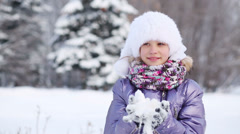 Stock Video Footage of Happy pretty girl in fur hat throws snow and smiles in park at winter
