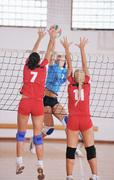 Girls playing volleyball indoor game Stock Photos