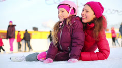Happy mother and daughter sit at ice rink after skating Stock Footage