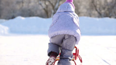Back of little girl in pink scarf and hat running with sledge Stock Footage