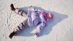 Little girl lies on snow and moves her arms and legs Stock Footage