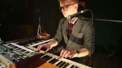Handsome man in glasses plays keyboard in night club with smoke Stock Footage