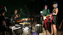 Rock band of four members play and sing in modern night club Stock Footage