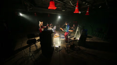 Band of four members play and sing in dark studio Stock Footage