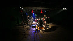 Musical group of four young members play and sing in dark studio Stock Footage