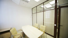Table and chairs in meeting hall with louvers on glass wall Stock Footage