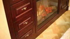 Wooden bookcase with built-in artificial fireplace in apartment - stock footage
