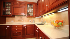 Kitchen with cupboards and fruits on table in cozy apartment Stock Footage
