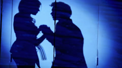Shadow of singing pair on wall with blue illumination Stock Footage
