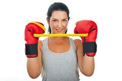 Woman holding centimeter between gloves - stock photo
