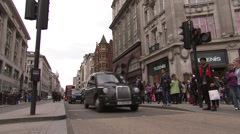Black cabs and Double Decker bus at intersection - stock footage
