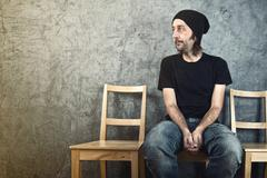 Man sitting on wooden chair and waiting - stock photo