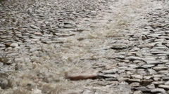 Stream of rain on the cobble road Stock Footage