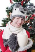 Woman in knitted hat and mitten under Christmas tree with cup Stock Photos