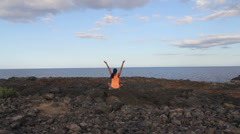 Yoga woman in the morning on a beach rock by the sea Stock Footage