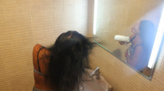 Beautiful woman drying her hair with hairdryer in the bathroom Stock Footage