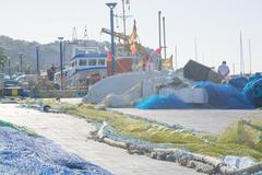 Nets on pier. fishing boat arrived in port Stock Photos
