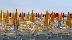closed umbrellas and deckchairs on the beach at sunset on the seashore - stock photo