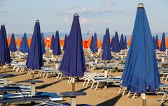 Closed umbrellas, blue and orange in a sun-drenched sea beach Stock Photos