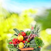 wire shopping basket with groceries - stock photo