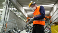 Stock Video Footage of Workman Puts on Protective Gloves Electronic Waste Plant